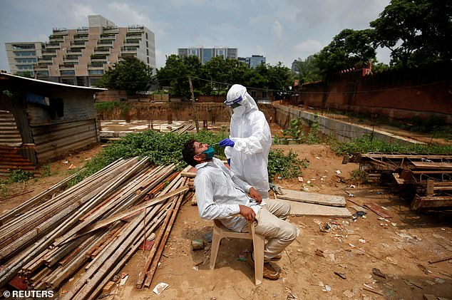 A healthcare worker wearing a protective suit takes a swab from a labourer at a construction site in Ahmedabad today