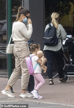 Cute: Meanwhile, little Rosie looked adorable in a white polo shirt, pink leggings and trainers, with the youngster clutching a doll as she walked