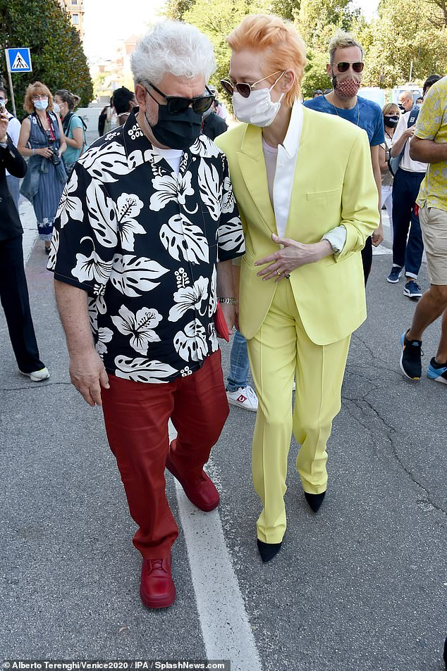 Safety: Pedro and Tilda wore masks as they made their way through the crowded street to the photocall