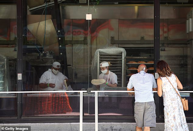 Visitors watch bakers make sourdough bread at Boudin Bakery in San Francisco