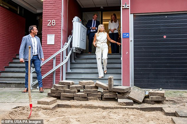 The day the Queen arrive the pavement outside the community centre had been dug up - with the filthy, dirt-covered street slabs contrasting against her crisp, white look
