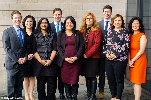 She resigned last month after the Seattle City Council's (pictured) vote to drop 100 officers out of 1,400 on the force.Only one council member, Kshama Sawant (third from left), voted against the budget package, saying it does not do enough to defund the police