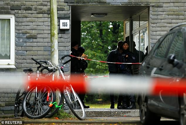 Police officers stand behind lines of tape at the entrance of the apartment block in Solingen