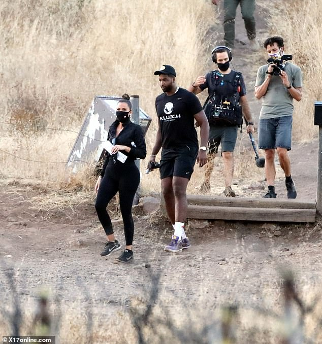Hiking fun:Several times, Khloe pulled down her mask while toting a large piece of paper, seemingly a map