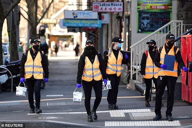 Pictured: Cleaners are seen walking through the street in Melbourne's CBD on Thursday