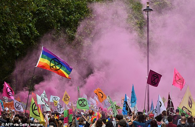 Extinction Rebellion flags flutter in the breeze amid pink smoke from flares during the protest on Horse Guards Road today