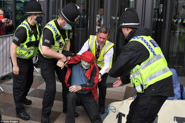 Police officers and security staff remove a man who tried to sit in front of the BBC Wales office in Central Square this afternoon