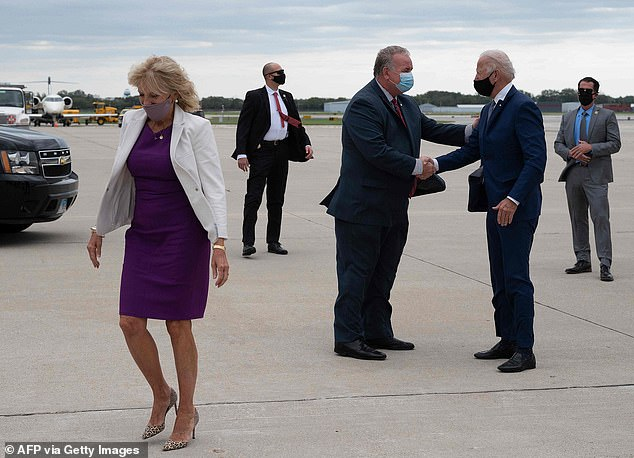 OOPS: Joe Biden slipped up and gave his aideBrian McPartlin a handshake as hedisembarked from the private plane he and Jill Biden (left) took from Delaware to Milwauke, Wisconsin, where he's meeting with Jacob Blake's family at an airport building