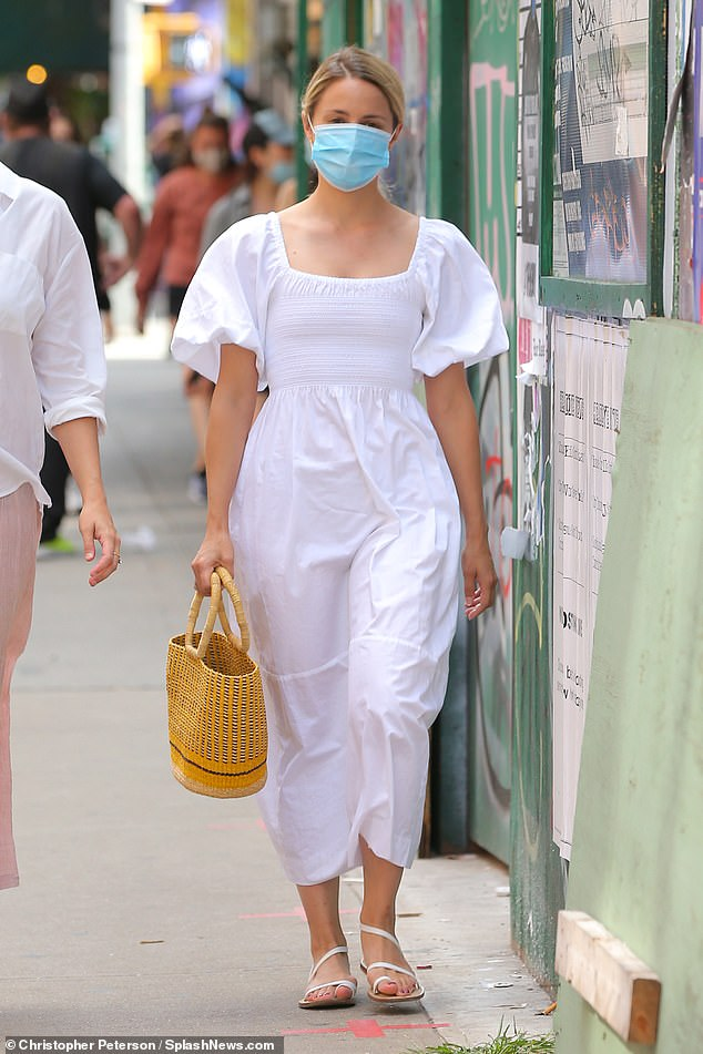 Summery look:Agron was wearing a white puff-sleeved midi-dress with matching sandals as she toted a straw bag