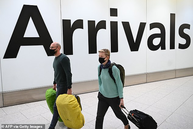 The Department for Transport, the Foreign Office, The Department of Health and the Home Office all had a hand in the Government's controversial quarantine policy. Pictured: Passengers wear face masks as they arrive with their luggage at Terminal 4 of London Heathrow Airport in west London