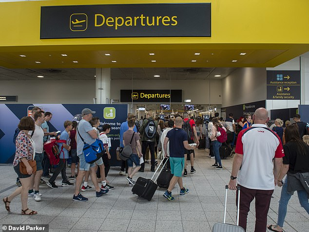 Pictured: Travellers at Gatwick airport make their way to the departure gate at the end of August last year