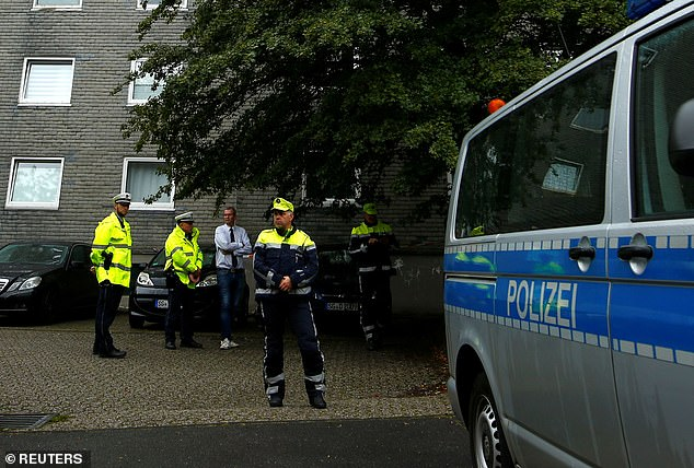 A group of uniformed people stand by a police van outside the apartment block in Solingen