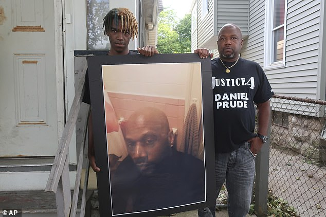 Daniel Prude's brother Joe, right, stands with his son, Armin, holding a photograph up of him outside their home on Thursday