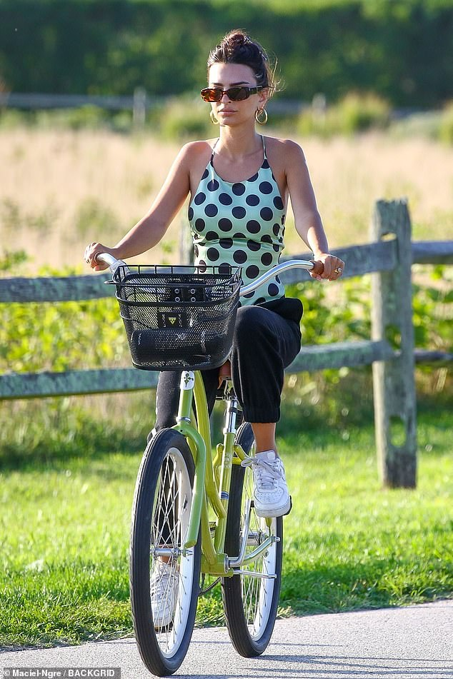 Quirky:The Blurred Lines video vixen looked ultra cool atop her bright green bicycle that had a black basket fastened to the front of it