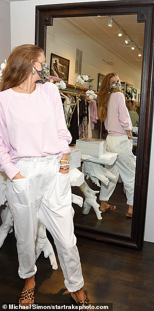 Another outfit: Inside the shop, Nina wore a different outfit in white cuffed pants and a pink crewneck sweatshirt
