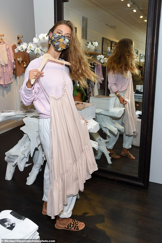 Options: She seemed to enjoy a series of pieces from the store, including a beige shift dress that she held up to herself in front of a mirror