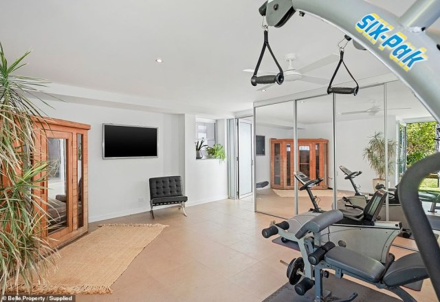 The home gym (pictured) is also impressive, filled with weights machines, floor-length mirrors and a TV screen so you can relax while you work out