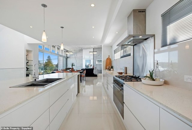 The open-plan house has a sleek Caesarstone kitchen (pictured) that has been fitted with countless modern appliances; there is also a wine cellar within the home