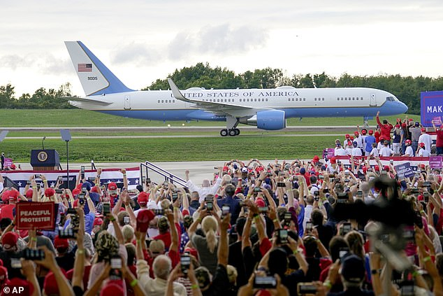 Air Force One lands as crowds cheer before President Donald Trump attends a campaign event at the Arnold Palmer Regional Airport