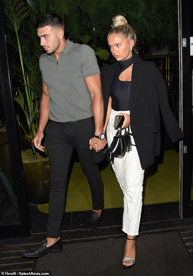 Glam:The Love Island star, 21, looked stylish in a form-fitting cut-out black top, which she wore tucked into a pair of white straight leg jeans with frayed detailing