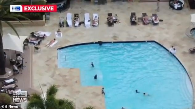 AFL WAGs and officials lounge by the Mercure's pool during their hotel quarantine on the Gold Coast