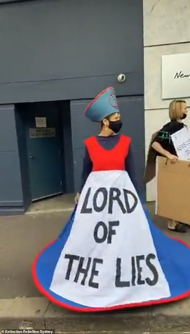 Angry demonstrators flanked the mounds of manure and waved placards urging the newspaper to 'tell the truth' (pictured, a protester wore an outfit that called News Corp the 'Lord of the Lies' on Friday)