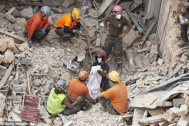 Rescue workers clear debris. A sniffer dog with a Chilean rescue crew responded to the suspected presence of a person in the rubble of a building damaged in the deadly explosion