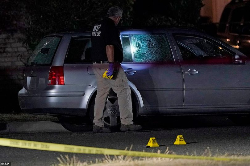 A Washington State Patrol official walks near evidence markers and a car with broken windows last night in Lacey, Wash. at the scene where Michael Reinoehl was killed as investigators moved in to arrest him