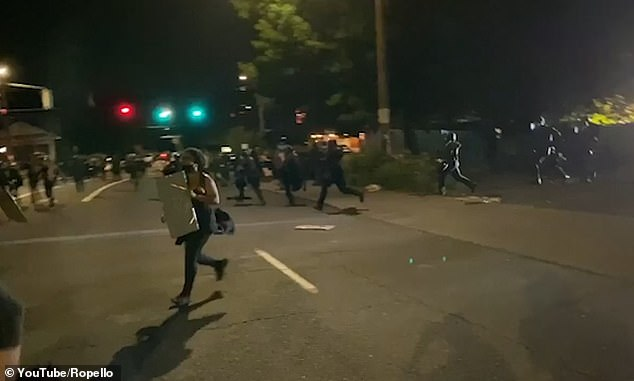 Antifa protesters flee from the scene carrying makeshift shields in Portland last night