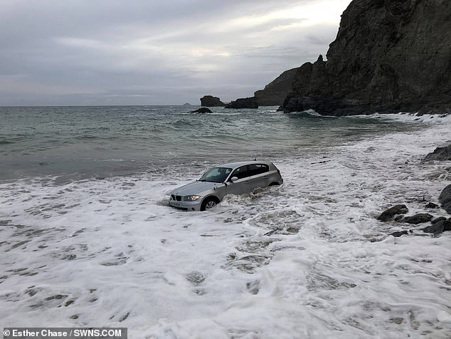 Car wash: This silver BMW was abandoned on St Agnes beach in Cornwall and was swamped by the tide