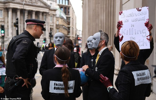 Protesters wearing signs reading 'faceless bureaucrats' pinned to the back of their suits talk to a police officer during demonstrations today