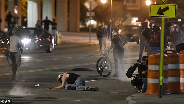 A protester falls to the ground amid a volley of chemicals fired by Rochester police
