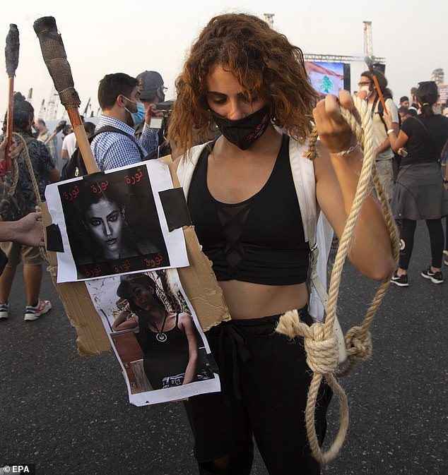Pictured: An anti-government protester carries pictures of victims and a hangman's noose as people mark the 1-month anniversary of the deadly Beirut explosion with demonstrations against the government, and demand punishment for those responsible