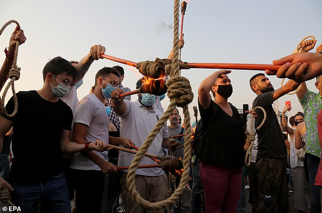 Pictured: Protesters in Beirut light torches while holding a hangmans noose during protests against those responsible for the explosion in the port of Beirut