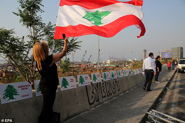 Pictured: A woman waves the Lebanese flag next to placards depicting the names of some of the victims of the Beirut explosion on August 4