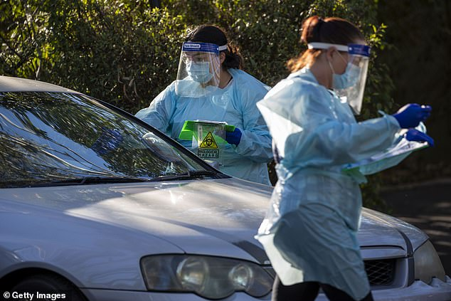 Nurses are seen doing COVID-19 testing at a drive-thru fever clinic in Ipswich on August 24, 2020