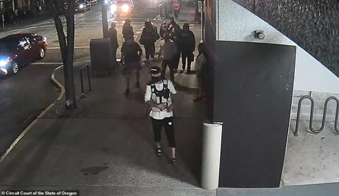 New surveillance images showReinoehl (front) walking in front of Aaron 'Jay' Danielson (behind him left in black shirt) moments before Danielson was shot dead in Portland on Saturday