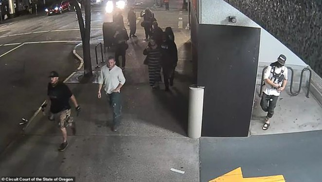 Reinoehl (right) ducks into a parking garage and waits for Danielson (far left) and his friend Chandler Pappas (next to him in white shirt) to walk past on the sidewalk