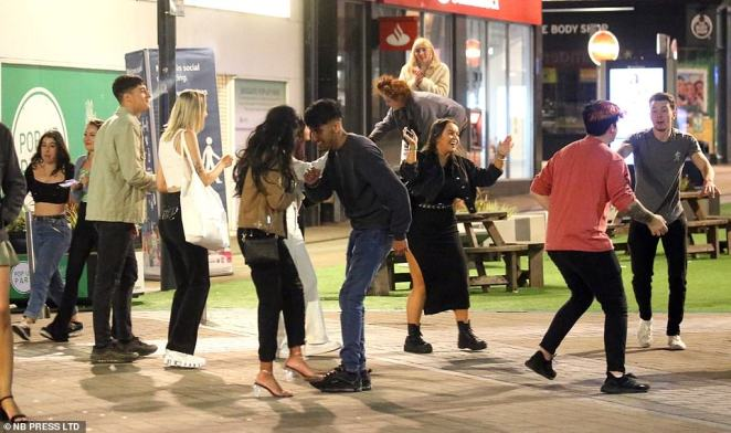 Partygoers are seen dancing in the street together and getting close and personal