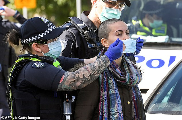 Police place a face mask on an arrested protester at the Shrine of Remembrance in Melbourne on Saturday