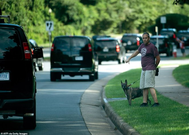 A man gives a thumbs down while watching Trump's motorcade arrive at the Trump National Golf Club in Sterling, Virginia, on Saturday