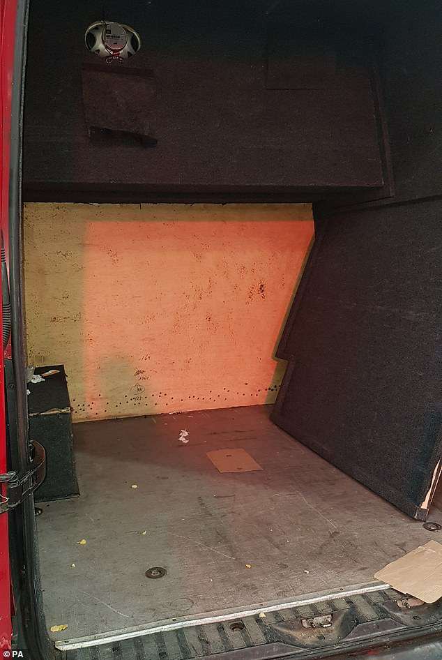 Officers found four people hidden in a false partition in the back of the van (pictured) and air holes had been drilled in the hiding place