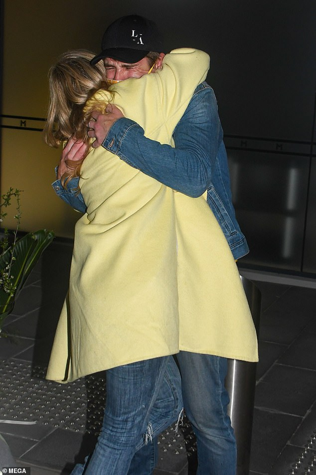 Emotional: Hugh wrapped his arms around Zoe as he prepared to return home, one week after initially returning a positive test for the virus