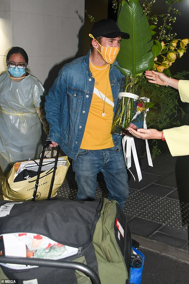 Home time: The Australian actor held a bouquet of flowers in one hand and his suitcase with the other as he walked out of the hotel