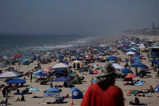 Huntington Beach in southern California was crowded on Saturday, with many seeking refuge from the sun with parasols