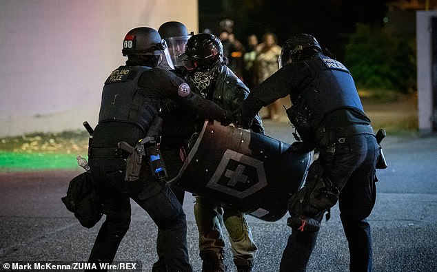 Officers wrestle a homemade shield from a protestor as they were arrested near the Portland Police Association building on North Lombard and North Campbell Streets in Portland, Oregon