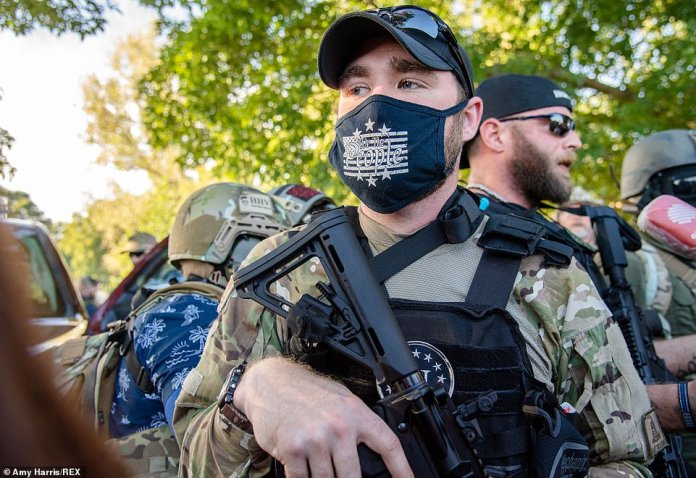 A member of a militia wears a mask bearing the slogan 'We the people' at a rally in Louisville, Kentucky on Saturday