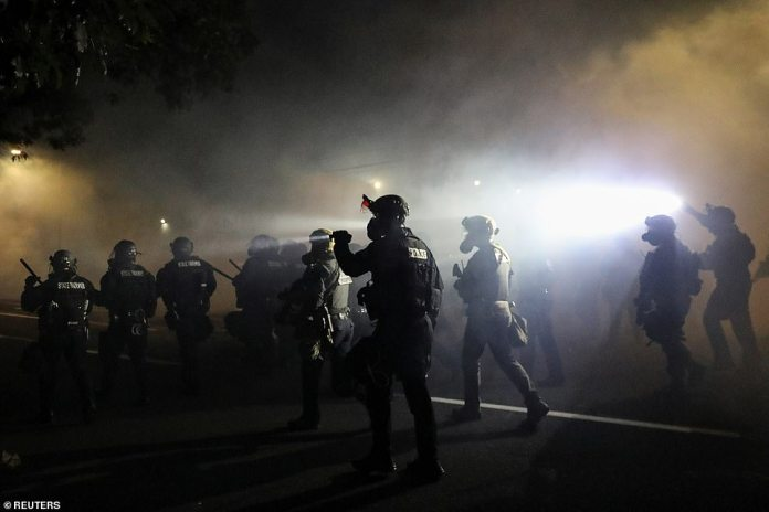 Police advance on protesters to clear a street after a Molotov cocktail was thrown on the 100th consecutive night of protests against police violence and racial inequality Portland