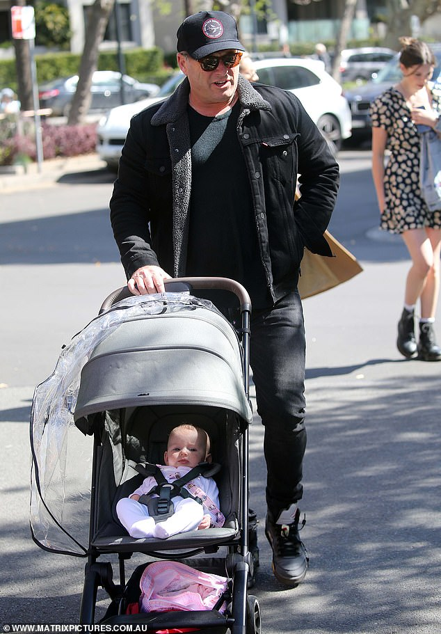 Cool dad: The Channel Nine star cut a cool and casual figure in a black T-shirt, skinny-leg jeans and sneakers
