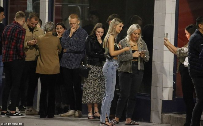 A crowd of people without face masks huddle in groups as they hit the streets to celebrate a night out at bars in the city